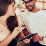 Portrait of happy young couple at cafe counter having discussion over a cup of coffee. Woman holding a digital tablet and man with cup of coffee.