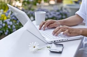 woman-using-white-laptop-lavender-background-sm